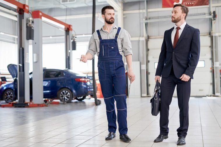 Homem de negócios conversando com funcionário em fábrica de automóveis