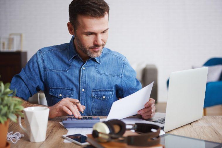 homem analisando um documento em frente ao computador e com uma calculadora na mão