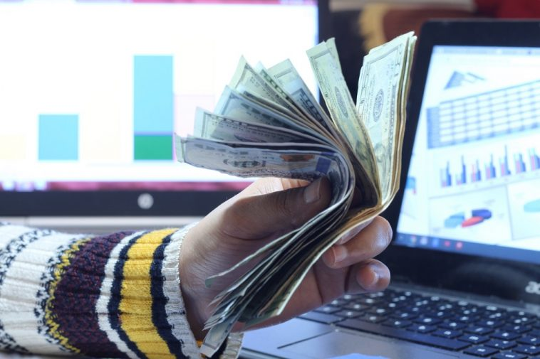 mão de uma pessoa segurando dinheiro em frente ao computador