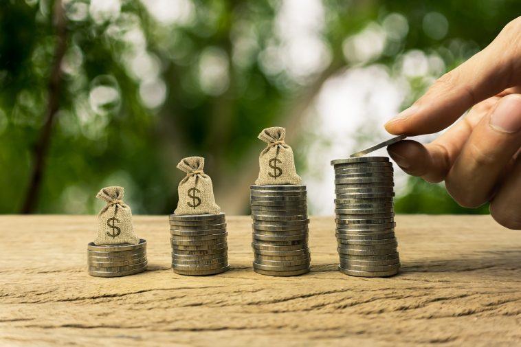 pilha crescente de moedas com sacos de dinheiro em cima delas