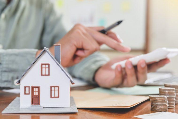homem fazendo conta na calculadora e destacado a frente a imagem de uma casa