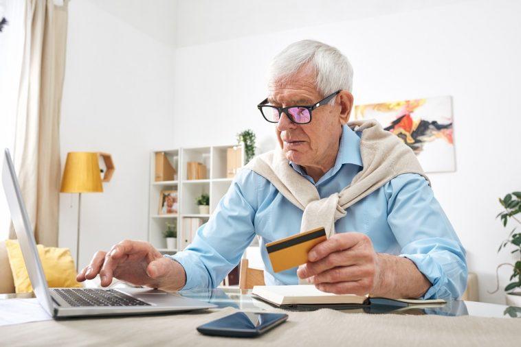 senhor idoso em frente ao computador com cartão de crédito