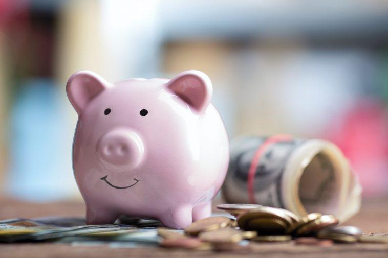 cofre de porquinho rodeado de moedas e notas de dinheiro