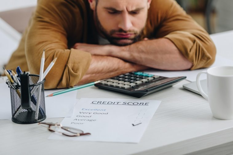 homem frustrado olhando para o score de crédito baixo em um mesa com outros papéis e calculadora