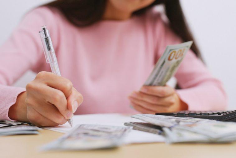 mulher fazendo anotações e na outra mão segurando dinheiro