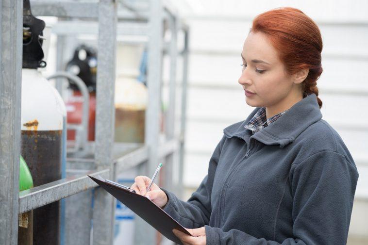mulher fazendo anotações em planilha em frente à um local de armazenamento de gás