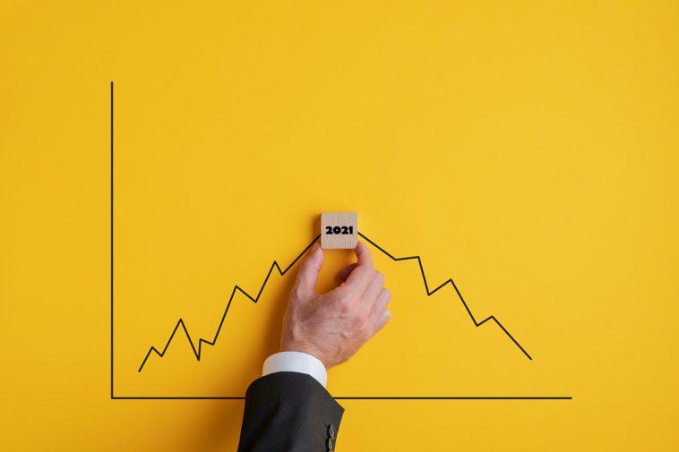 mão de um homem segurando uma placa de 2021 no meio de um gráfico de alta e baixa nos valores
