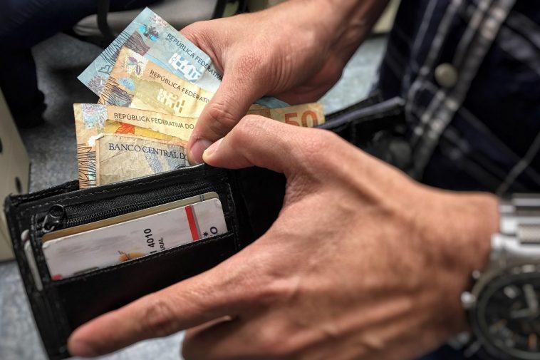 homem contando dinheiro na carteira