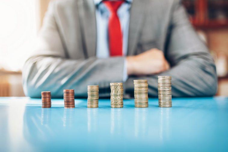 homem de negócios em frente a uma pilha crescente de moedas