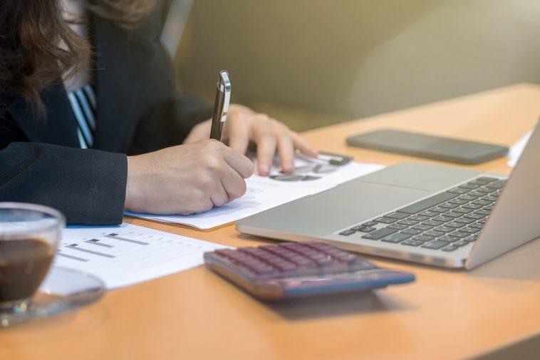 mulher fazendo contas e escrevendo em papéis em frente ao computador