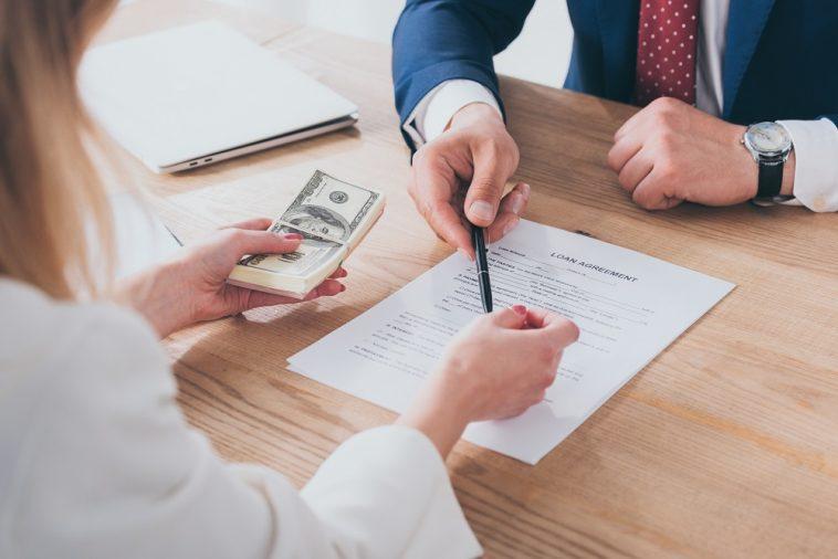 homem de negócios pedindo para moça assinar contrato, ela está com dinheiro na mão
