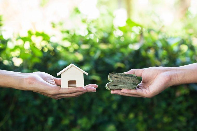 uma mão segurando uma casa e a outra oferecendo dinheiro
