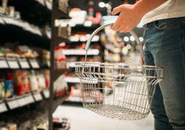 homem com cesta de compras vazia na mão olhando para a prateleira no supermercado