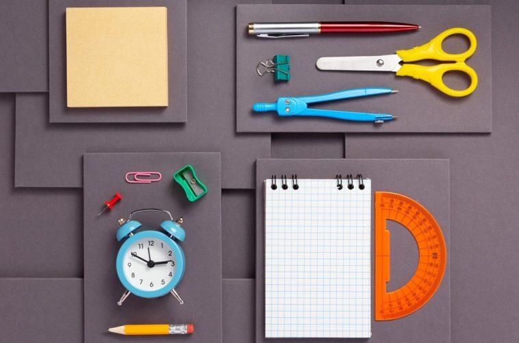 imagem de objetos e itens escolares espalhados sobre uma mesa preta, como compasso, relógio, tesoura e etc.