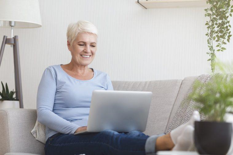 idosa no computador digitando com aspecto feliz