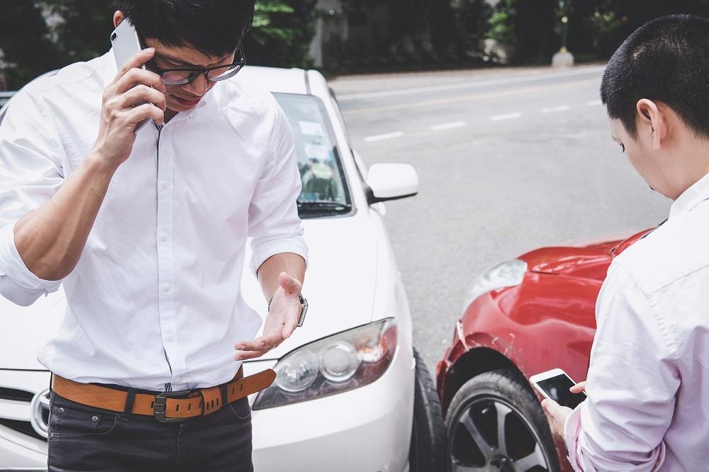 Dois homens envolvidos em acidente de trânsito, um falando ao celular e outro acessando a internet