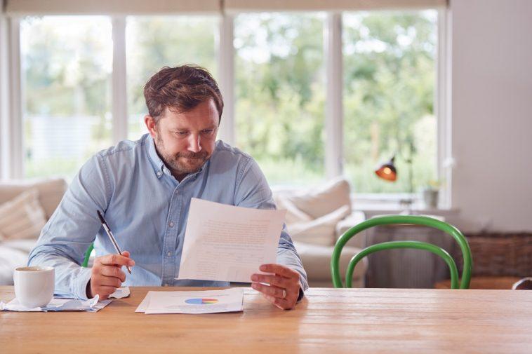 homem sentado a mesa anotando suas finanças pessoais