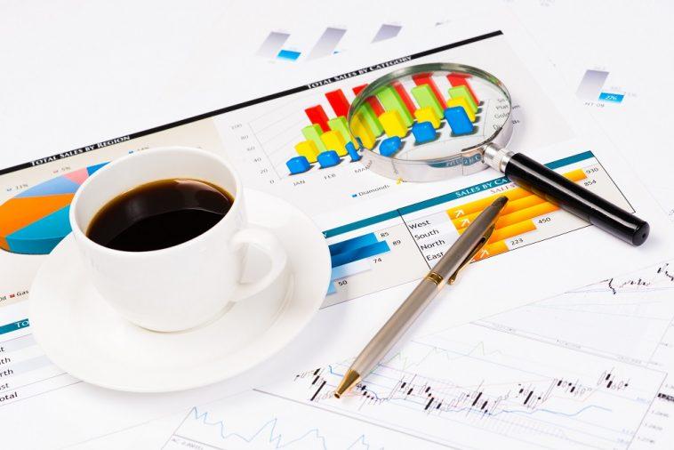 xícara de café em cima de um relatório de dados com gráfico de barras