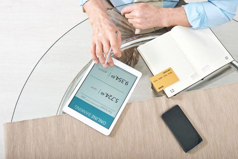 mão masculina mexendo em tablet escrito banco online ao lado de um caderno com cartão de crédito