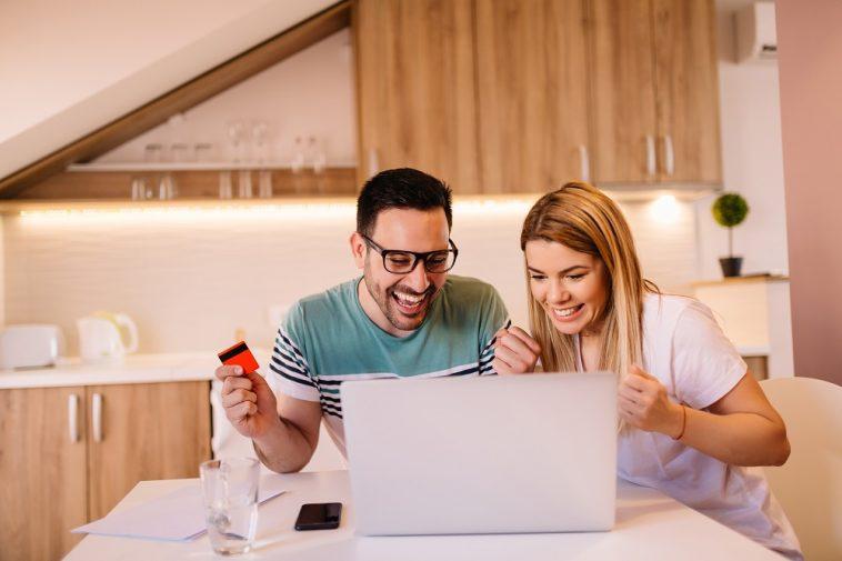 casal em frente ao computador comemorando com um cartão de crédito na mão