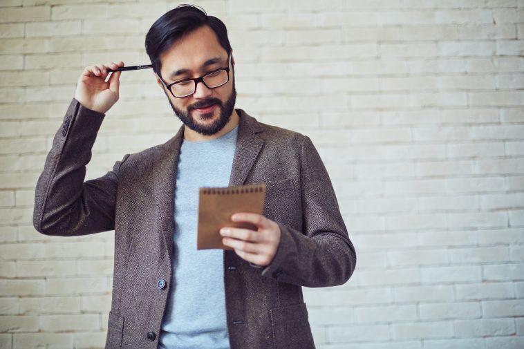 homem asiático com um lápis coçando a cabeça olhando para uma caderneta