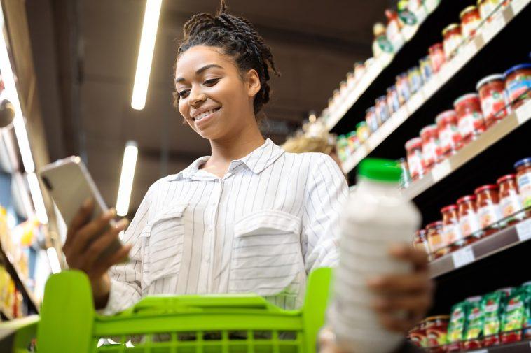 moça jovem mexendo no celular enquanto segura um carrinho de compras no supermercado