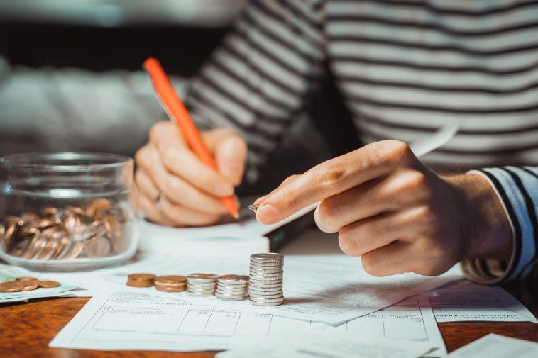 mulher contando moedas e calculando contas