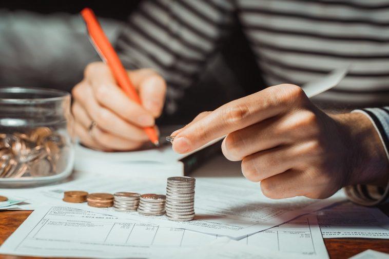 mão de mulher empilheiramendo moedas e fazendo contas