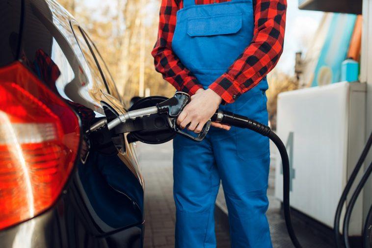 frentista de uniforme azul segurando a bomba de gasolina para encher o tanque de um carro