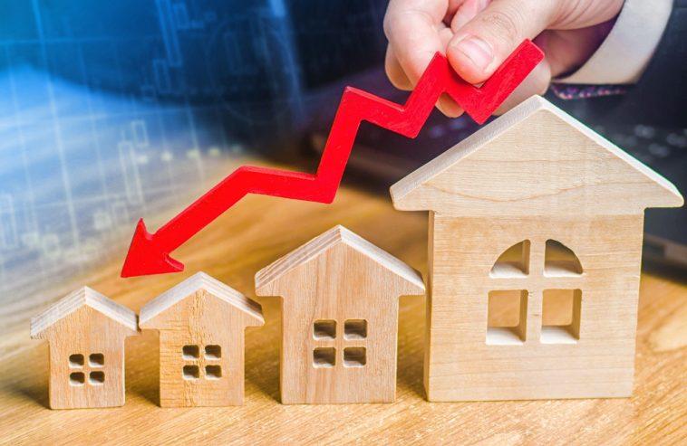 investidor segurando uma seta decrescente sobre imóveis