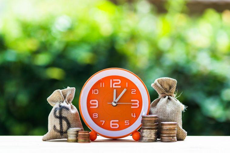 dois sacos de dinheiro ao lado de um relógio e de moedas