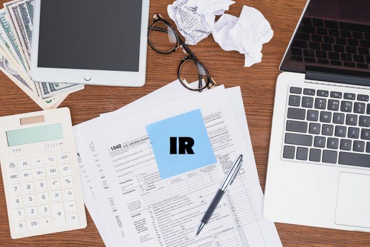 papéis sobre uma mesa e um post-it com a palavra IR
