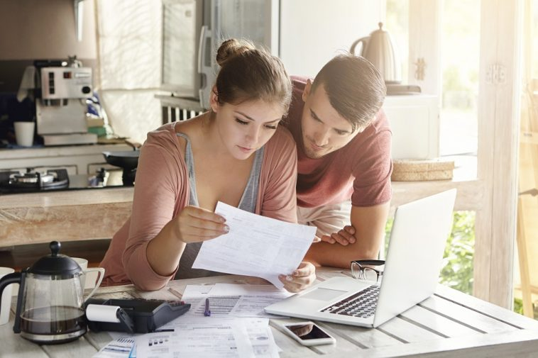 casal jovem lendo um documento em frente ao computador
