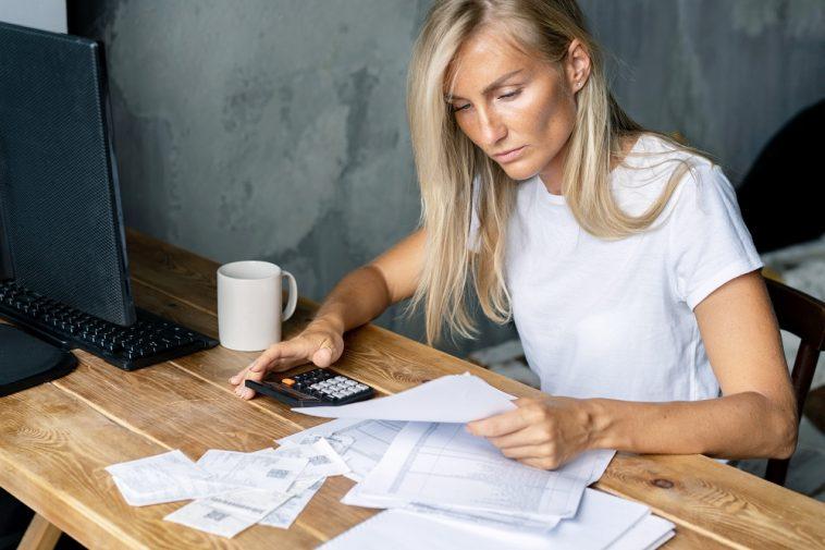 mulher empreendedora mexendo em documentos e com calculadora na mão