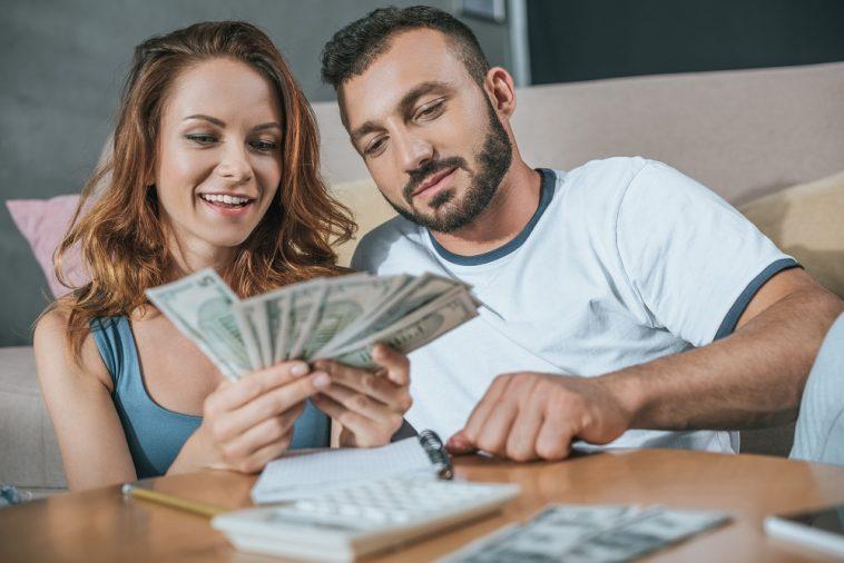 casal fazendo as contas para o orçamento familiar e contando o dinheiro que está sobrando