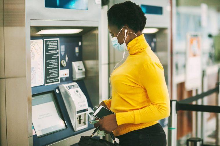 Mulher africana vestindo uma máscara protetora retira dinheiro de um cartão bancário