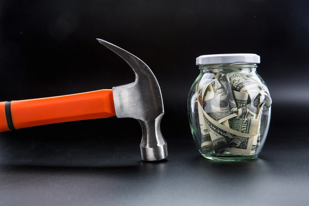 Martelo contra jarro cheio de dólares, simbolizando o momento da retirada de dinheiro da reserva de emergência