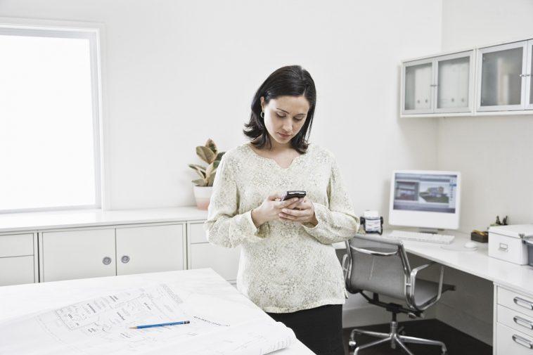 Mulher hispânica trabalhando no telefone celular