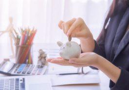 mulher no escritório inserindo uma moeda em um cofre de porquinho branco pequeno para poupança