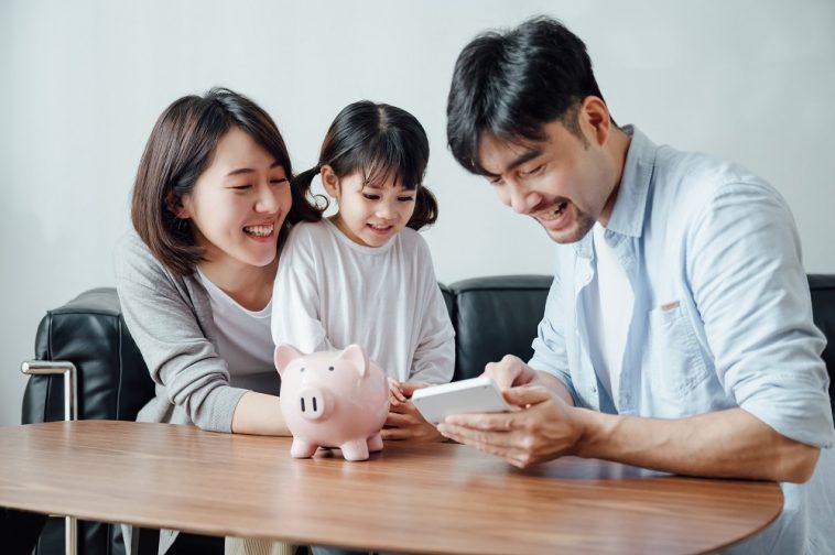 Pais ensinando filha para economizar dinheiro em casa