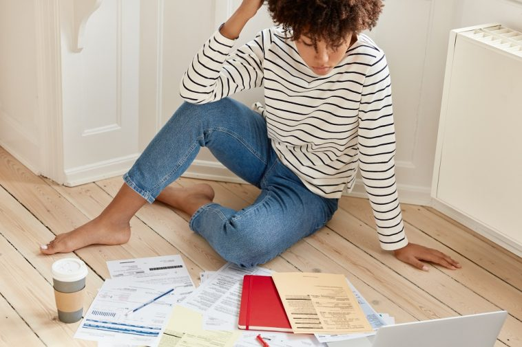 mulher sentada no chão olhando para várias contas