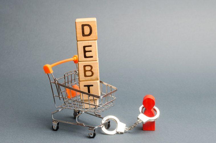 Blocos de madeira com a palavra Dívida em um carrinho de supermercado e uma estatueta humana amarrada por algemas