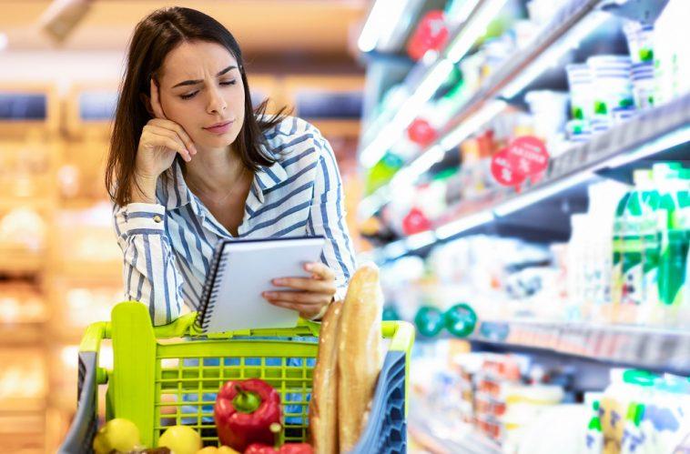mulher olhando desconfiada para a lista de compras apoiada em um carrinho de compras no supermercado