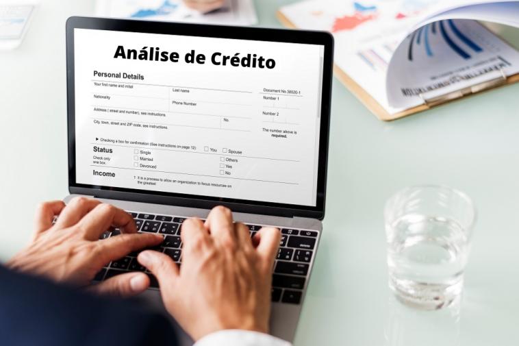 homem mexendo no computador fazendo uma análise de crédito