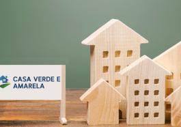 Um cartaz escrito programa casa verde e amarela e casas de madeira. Conceito de planejamento e financiamento imobiliário
