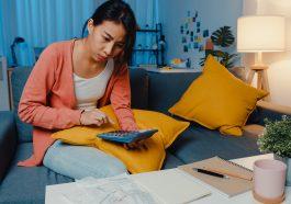 mulher asiática estressada calculando as taxas de juros de cartão de crédito e pensando em fazer um empréstimo