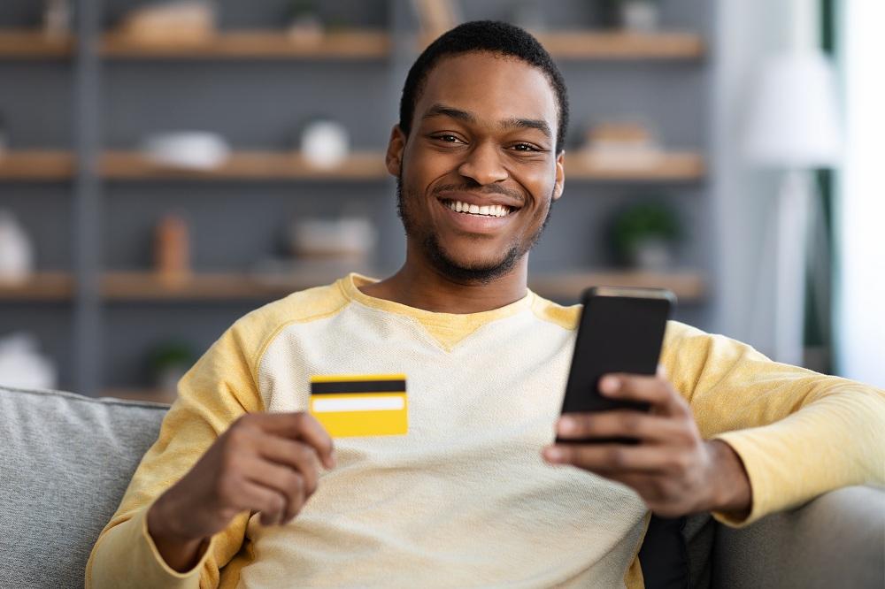 Homem afro-americano alegre com cartão de crédito sem anuidade