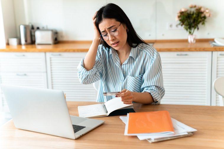 mulher olhando assustada para o seu cartão de crédito clonado