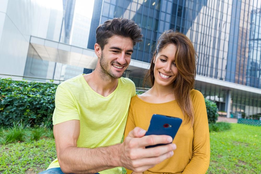 Casal uso do celular em conjunto para ver o calendário da segunda parcela do auxílio emergencial 2021 atualizado