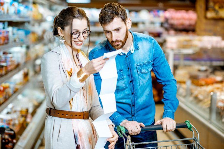 casal conferindo compras no supermercado com CPF na nota fiscal